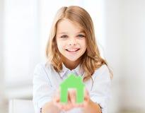Dziewczyna trzyma zielonego papieru dom Fotografia Stock