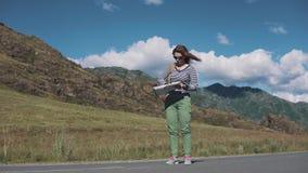 Dziewczyna turysta no może podołać z papierową mapą przez silnego wiatru kobieta podróżnik z plecakiem wewnątrz i mapą zbiory