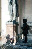 Dziewczyna turysta przy marmurowymi statuami Atlanta ` s chwyta sufit Nowy erem, St Petersburg, Rosja obrazy stock