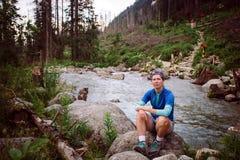 Dziewczyna turysta Sedin na kamieniu blisko halnej rzeki w wysokim Tatras w Sistani Ubierający w błękitnej koszulce, szarzy skrót Obraz Stock