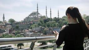 Dziewczyna turysta stoi obrazki na pastylka pięknych widokach miasto i bierze indyk zbiory
