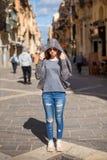 Dziewczyna turysta w cajgach z szkłami i kapiszonie w postaci kobry stoi samotnie po środku wąskich ulic Obraz Stock