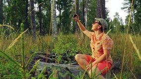 Dziewczyna turysta w okularach przeciwsłonecznych i baseball nakrętce w lesie na słonecznego dnia obsiadaniu na spadać obrazkach  zbiory wideo