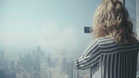 Dziewczyna turysta w pasiastej koszulowej pozyci przy okno i fotografującej zdjęcie wideo