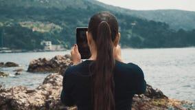 Dziewczyna turysty stojaki na plaży i biorą obrazki na pastylek drzewach i skałach zdjęcie wideo