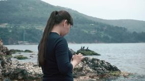 Dziewczyna turysty stojaki na skalistej plaży podziwia widok i trzyma pastylkę, zdjęcie wideo