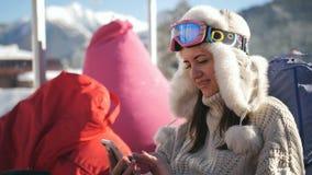 Dziewczyna używa mądrze telefonu obsiadanie w kawiarni przy ośrodkiem narciarskim Młoda kobieta relaksuje przy wysokogórskim ośro zdjęcie wideo