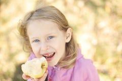 Dziewczyna uśmiecha się jabłka w jesieni na naturze i je chodzi outdoors Obraz Stock