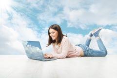 Dziewczyna używa bezprzewodowego laptop nad nieba tłem.  Zdjęcia Stock