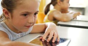 Dziewczyna używa cyfrową pastylkę w sala lekcyjnej