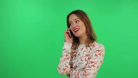 Dziewczyna używa mobilnego telefonu komórkowego typ ekran, mówienie i uśmiech nad tłem wiadomość dotyka, zbiory