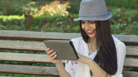 Dziewczyna używa pastylkę na ławce zbiory
