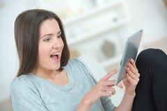Dziewczyna używa pastylki zdziwionego wyrażenie na twarzy obrazy stock