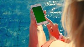 Dziewczyna używa pionowo telefon komórkowy zieleni ekran podczas gdy relaksujący blisko basenu Ręki trzyma smartphone chromu kluc zbiory