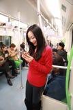 Dziewczyna używa telefon komórkowego metrem podczas gdy podróż, kobieta używa jej telefon komórkowego w metrze obraz royalty free