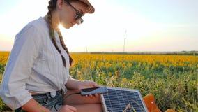 Dziewczyna używa wiszącą ozdobę i panelu słonecznego komunikuje w ogólnospołecznej sieci na tła polu, młodej kobiety wyszukiwać k zdjęcie wideo