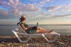 Dziewczyna ubiera w kapeluszu sukni i, trzyma komputer, freelancer na bÅ'Ä™kitnym morzu i nieba backgr, i kÅ'ama na bryczki longu zdjęcie royalty free