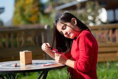Dziewczyna ubierająca w czerwonym obsiadaniu w ogródzie Fotografia Royalty Free