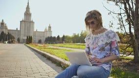 Dziewczyna uczeń pracuje z laptopem na kwadracie na tle Lomonosov Moskwa stanu uniwersytet zbiory