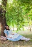 Dziewczyna uczeń spadał sen pod drzewem z książką Obrazy Stock