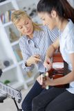 Dziewczyna uczenie dlaczego bawić się gitarę z nauczycielem obrazy stock