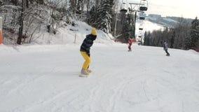 Dziewczyna uczenie jechać zjazdowego skłon na snowboard Młoda dziewczyna uczy się snowboard Kamera na ruchu zbiory wideo