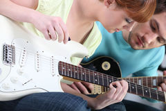 Dziewczyna uczy się bawić się gitarę Zdjęcia Royalty Free