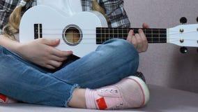 Dziewczyna uczy się bawić się ukulele, muzykalny hobby, dziecko twórczość, czas wolny zbiory