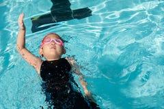 Dziewczyna uczy się dlaczego pływać w dopłynięcie klasie Fotografia Stock