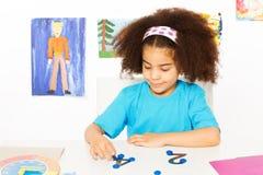 Dziewczyna uczy się liczyć stawia błękitne monety Obraz Stock