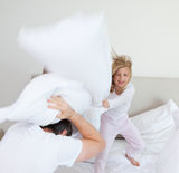 Dziewczyna uderza jej ojca z poduszką Zdjęcia Stock