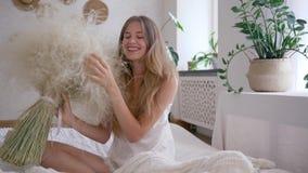 Dziewczyna uwalnia alergia chwyta bukiet piórkowe trawy i ono uśmiecha się na kamery obsiadaniu na łóżku w piżamie zbiory wideo