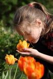 Dziewczyna wącha kwiaty w ogródzie fotografia royalty free