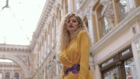 Dziewczyna w żółtej sukni pozuje dla kamery w przejściu czerwonym żakiecie i zbiory