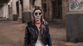Dziewczyna w ślubnej sukni w kurtce z makijażem w formie czaszka i zdjęcie wideo