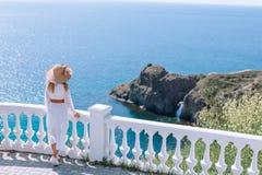 Dziewczyna w śnieżnobiałej sukni i kapeluszu z szerokim rondem podziwia widok morze i skały obraz stock