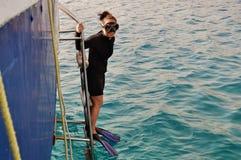 Dziewczyna w akwalung przekładni gotowej skakać w wodzie obrazy stock