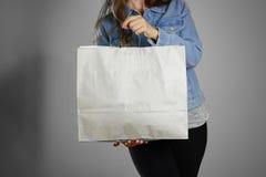 Dziewczyna w błękitnego drelichowego koszulowego mienia pustej czystej papierowej torbie Fotografia Stock