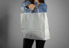 Dziewczyna w błękitnego drelichowego koszulowego mienia pustej czystej papierowej torbie Fotografia Royalty Free