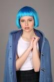 Dziewczyna w błękitnej peruce i żakiet kompresuje jej rękę z bliska Szary tło Fotografia Stock