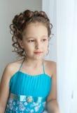 Dziewczyna w błękitnej sukni i przyglądający out okno Fotografia Royalty Free