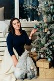 Dziewczyna w błękitnej sukni w nowego roku wystroju blisko dekorującej choinki Obraz Stock