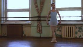 Dziewczyna w błękitnym leotard i błękitni baletniczej spódnicy chwyty omijamy w rękach i robimy battement tandu podczas choreogra zbiory wideo