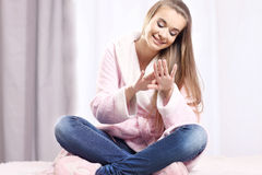 Dziewczyna w bathrobe obsiadaniu na łóżku Obraz Stock