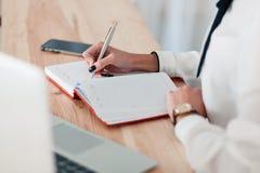 Dziewczyna w białej bluzce siedzi przy stołem z laptopem i pisze w czerwonym notatniku fotografia stock