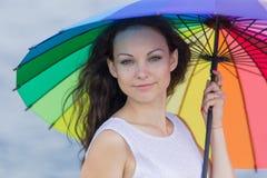 Dziewczyna w białej sleeveless sukni pozuje z tęcza parasolem Zdjęcia Stock