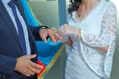 _ Dziewczyna w białej sukni i facecie w kostiumu Fornal stawia pierścionek na pannie młodej Proces małżeństwo i zdjęcie stock