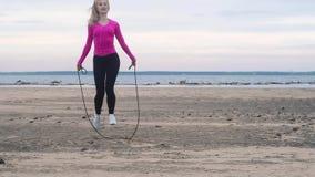 Dziewczyna w białych sneakers, czarni leggings, różowej koszulki skokowa arkana na plaży Sprawność fizyczna w natury lata chmurny zbiory wideo