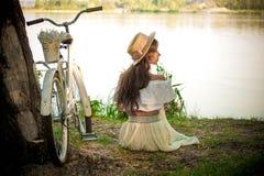 Dziewczyna w białym i białym bicyklu na tle rzeka obrazy stock