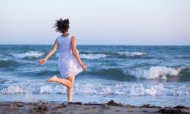 Dziewczyna w biel sukni bieg wzdłuż plaży fotografia stock